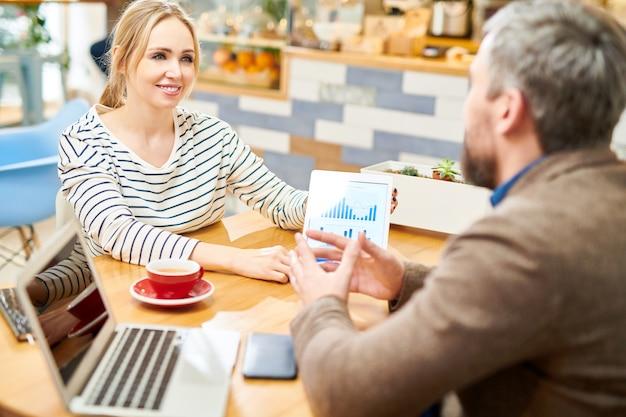 Jovem analista ou corretor de sucesso com tablet, olhando para a explicação do colega sobre gráficos eletrônicos