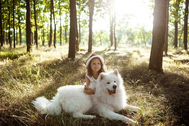 Jovem andando, brincando com o cachorro no parque ao pôr do sol.