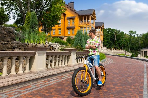 Jovem andando de bicicleta colorida e amarela passando por uma casa pintada de amarelo em uma estrada pavimentada de tijolos