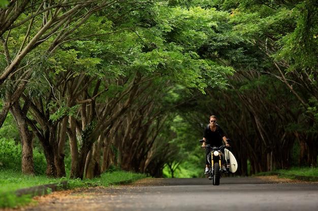 Jovem andando de moto com uma prancha de surf