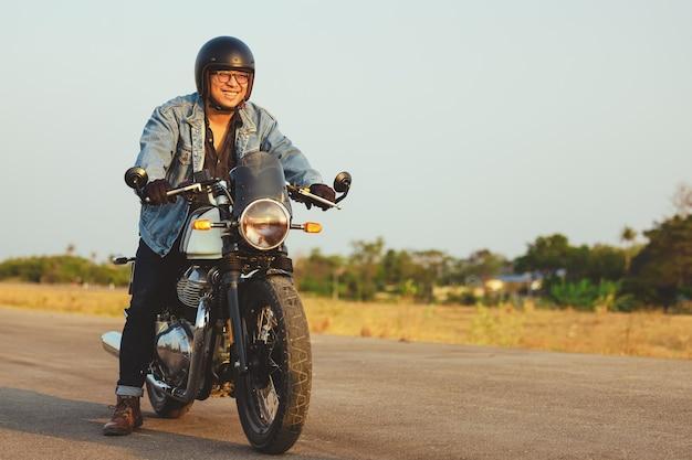 Jovem andando de moto grande no asfalto contra, o homem moto tem liberdade