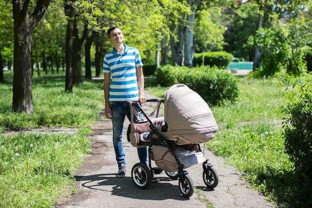 Jovem andando em um parque de outono com um carrinho de bebê