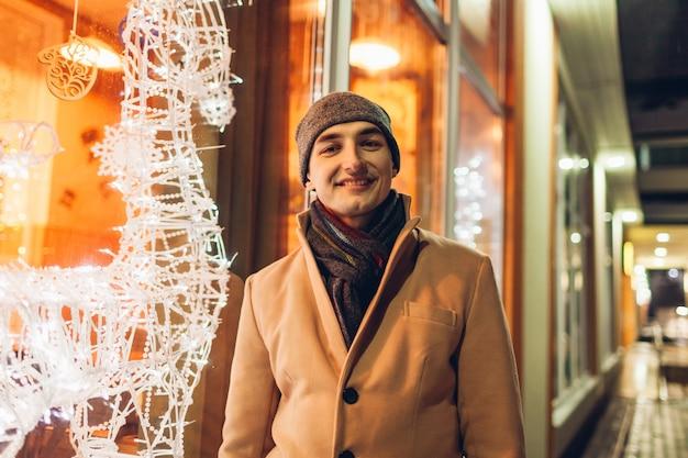 Jovem andando na cidade por vitrines de natal decoradas à noite e olhando para a câmera.