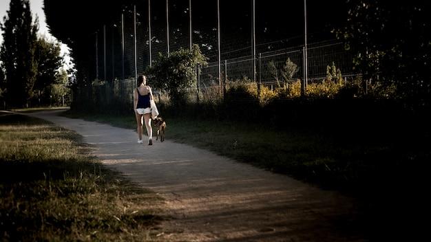 Jovem andando no parque ao longo do caminho com seu cachorro em uma bela noite