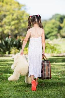 Jovem andando no parque com uma mala e ursinho de pelúcia