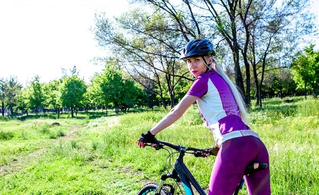 Jovem, andar de bicicleta esportiva no parque em um dia ensolarado, a garota está envolvida no ciclismo