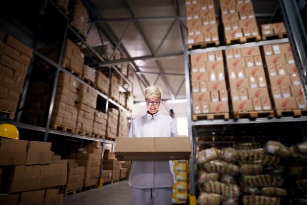 Jovem animada adorável trabalhadora está segurando uma caixa grande perto de pilhas de caixas em uma área de armazenamento da fábrica.
