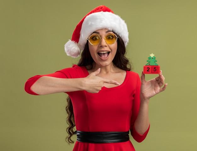 Jovem animada com chapéu de papai noel e óculos segurando e apontando para um brinquedo da árvore de natal com um par