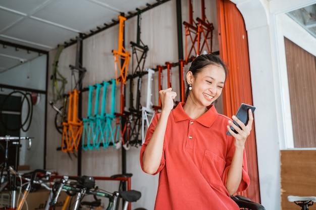 Jovem animada olhando para a tela do celular na loja de bicicletas