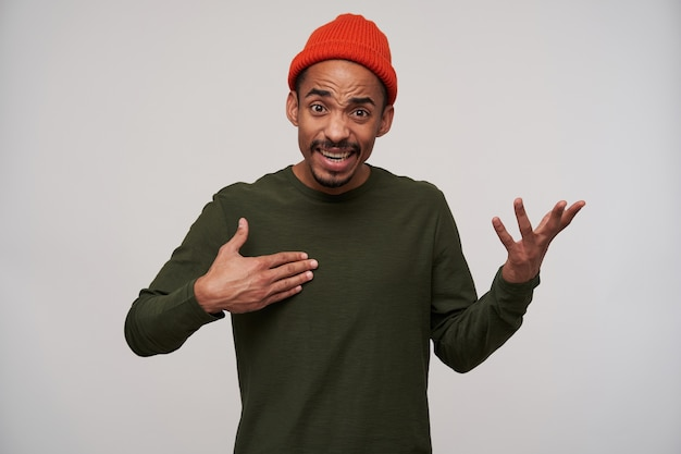 Jovem animado, barbudo, cabelo escuro, pele escura levantando as palmas das mãos com rosto confuso, usando chapéu vermelho e suéter cáqui enquanto posava em branco