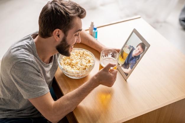 Jovem animado bebendo cerveja com um amigo e comendo pipoca enquanto usa o chat por vídeo no tablet