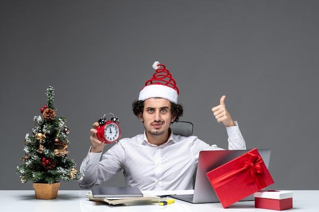 Jovem, animado, chocado, empresário com chapéu de papai noel e mostrando o relógio trabalhando sozinho, sentado no escritório em fundo escuro