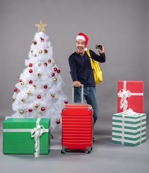 Jovem animado com chapéu de papai noel segurando uma mala vermelha mostrando um cartão cinza