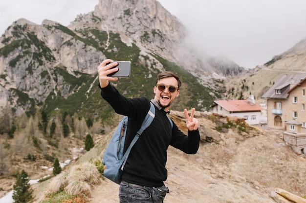 Jovem animado com corte de cabelo curto posando nas montanhas com casa aconchegante