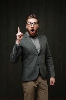 Jovem animado de terno casual e óculos apontando para cima e tendo uma ideia isolada no fundo preto de madeira