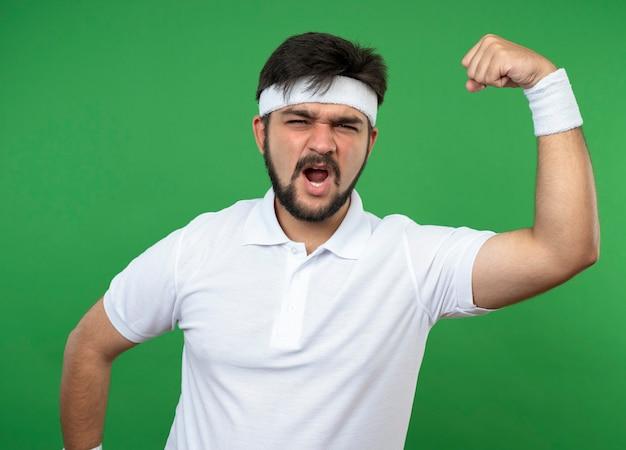 Jovem animado e esportivo usando bandana e pulseira, mostrando um gesto forte