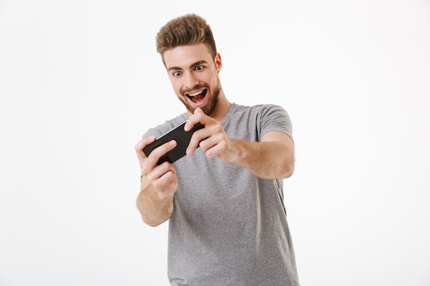 Jovem animado joga pelo telefone celular.