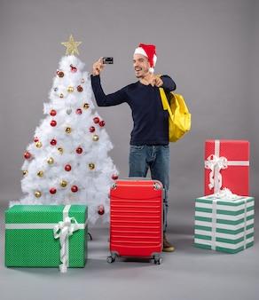 Jovem animado segurando um cartão em pé perto da árvore de natal e presentes em cinza