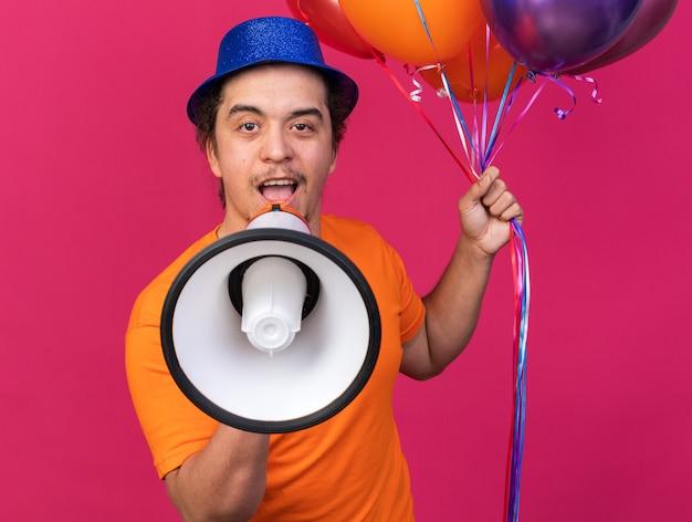 Jovem animado usando chapéu de festa segurando balões falando no alto-falante isolado na parede rosa
