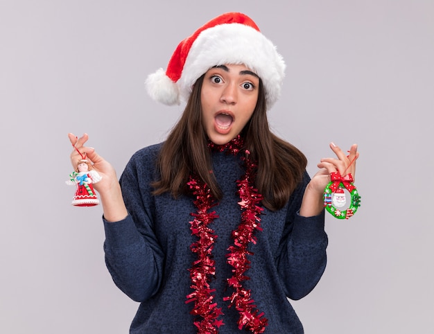 Jovem ansiosa caucasiana com chapéu de papai noel e guirlanda no pescoço segurando brinquedos da árvore de natal