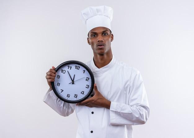 Jovem ansiosa cozinheira afro-americana com uniforme de chef segurando o relógio com as duas mãos isoladas no fundo branco com espaço de cópia