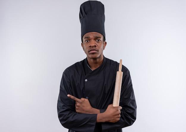 Jovem ansiosa cozinheira afro-americana em uniforme de chef segurando o rolo e aponta para o lado isolado no fundo branco com espaço de cópia