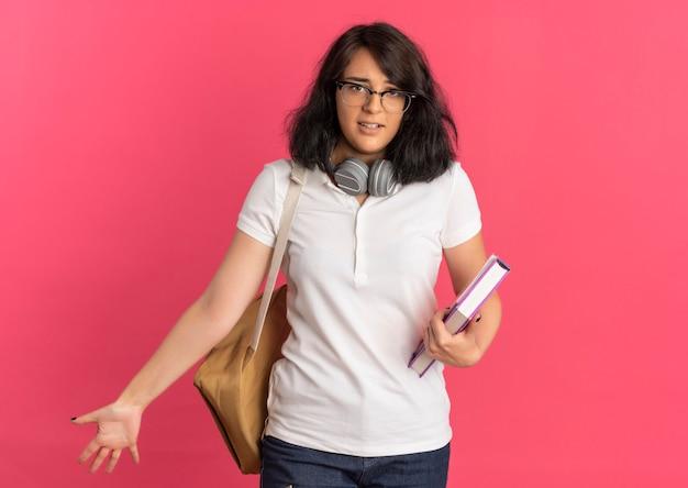 Jovem ansiosa e bonita caucasiana colegial de óculos e bolsa traseira com fones de ouvido no pescoço segurando livros rosa com espaço de cópia