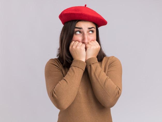 Jovem ansiosa e bonita caucasiana com chapéu boina coloca os punhos no queixo olhando para o lado isolado na parede branca com espaço de cópia