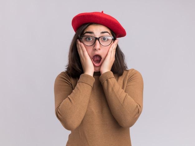Jovem ansiosa e bonita caucasiana com chapéu boina e óculos óticos coloca as mãos no rosto isolado na parede branca com espaço de cópia