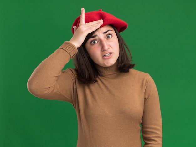 Jovem ansiosa e bonita caucasiana com chapéu de boina coloca a mão na cabeça isolada em uma parede verde com espaço de cópia