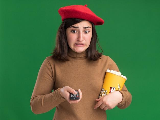 Jovem ansiosa e bonita caucasiana com chapéu de boina segurando o controle da tv e um balde de pipoca