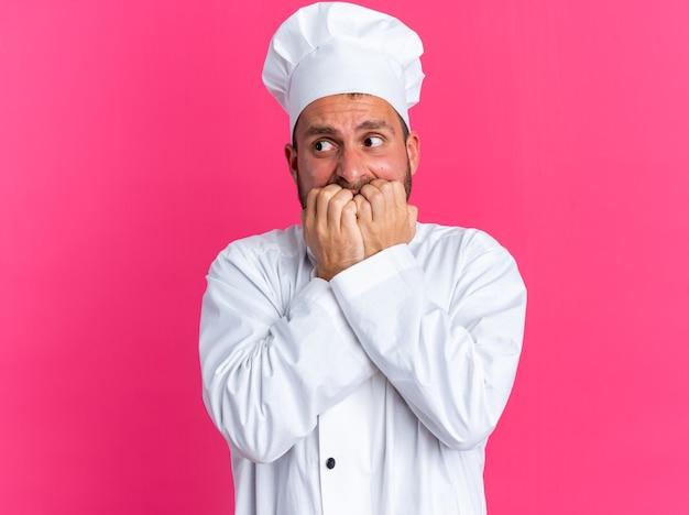 Jovem ansioso, caucasiano, cozinheiro, com uniforme de chef e boné olhando para o lado, mordendo os dedos