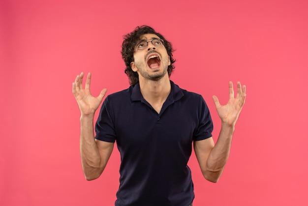 Jovem ansioso de camisa preta com óculos ópticos levanta as mãos e olha para cima, isolado na parede rosa