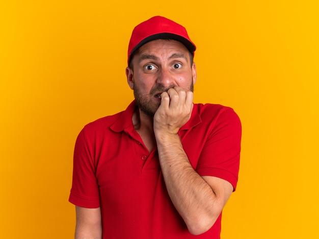 Jovem ansioso, entregador, caucasiano, de uniforme vermelho e boné mordendo os dedos, olhando para a câmera, isolada na parede laranja