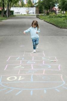 Jovem ao ar livre brincando de amarelinha