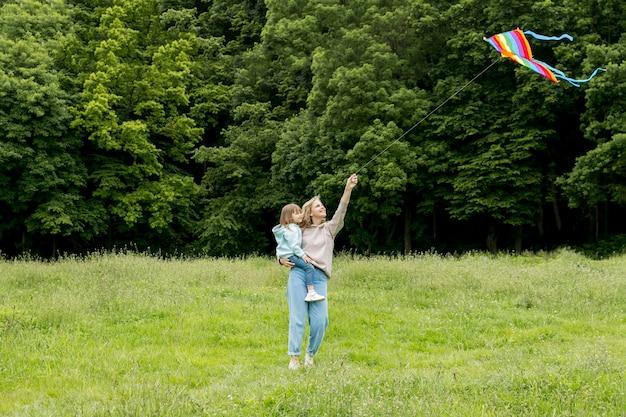 Jovem ao ar livre e mãe brincando com pipa