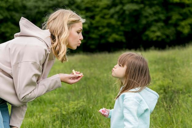 Jovem ao ar livre e mãe soprando beijos