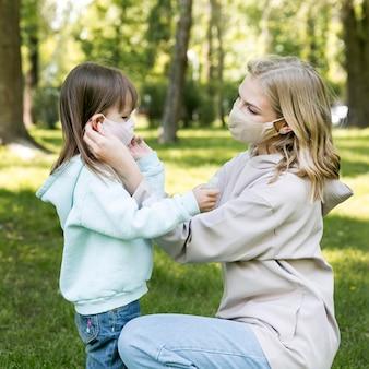 Jovem ao ar livre e mãe vestindo máscaras