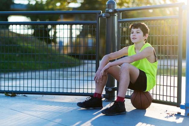 Jovem ao ar livre sentado em uma bola de basquete em uma quadra de rua com bola