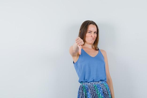 Jovem aparecendo o polegar enquanto azedando o rosto na blusa, saia e parecendo descontente, vista frontal.