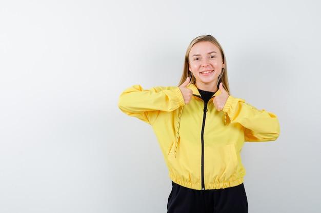 Jovem, aparecendo polegares para cima em jaqueta amarela, calças e olhando alegre, vista frontal.