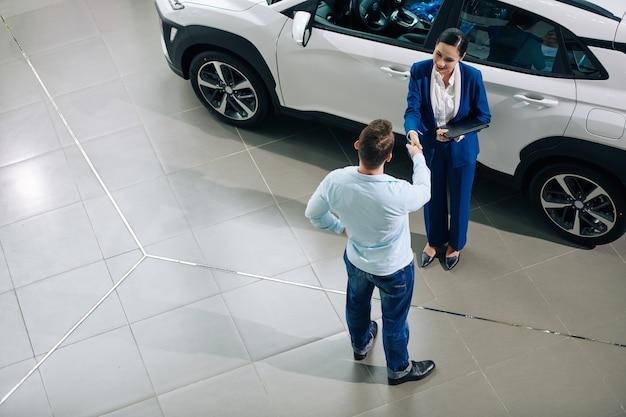 Jovem apertando a mão de uma gerente de concessionária que o ajudou a comprar um carro novo