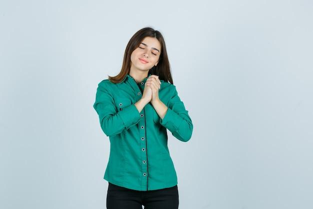 Jovem apertando as mãos sobre o peito na blusa verde, calça preta e parecendo alegre. vista frontal.