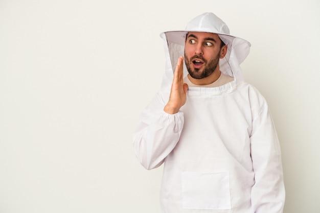 Jovem, apicultor, caucasiano, isolado no fundo branco, contando uma notícia secreta sobre a travagem e olhando para o lado
