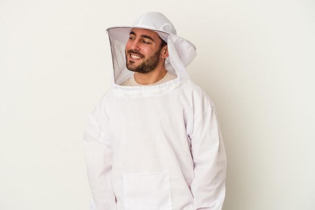 Jovem apicultura homem caucasiano isolado no fundo branco parece de lado sorrindo, alegre e agradável.