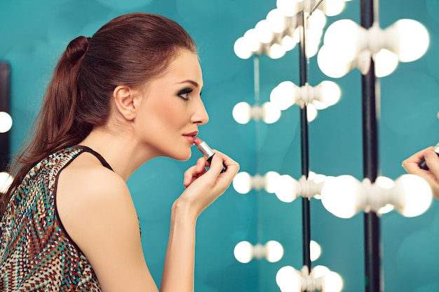 Jovem aplicando batom em frente a um espelho