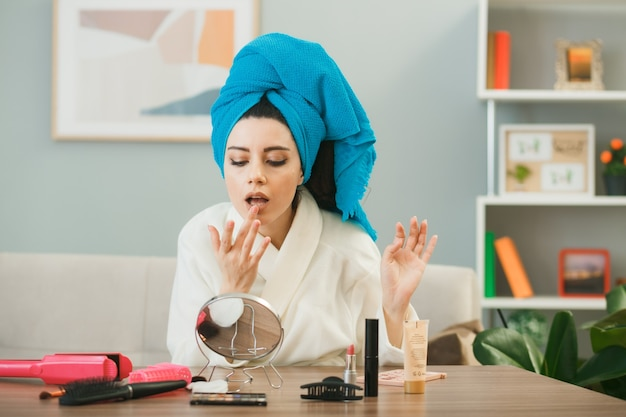 Jovem aplicando gloss labial enrolado em uma toalha, sentada à mesa com ferramentas de maquiagem na sala de estar