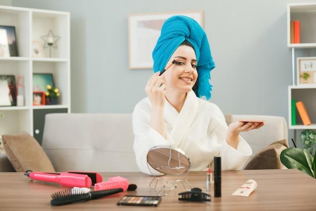 Jovem aplicando sombra com pincel de maquiagem enrolado em uma toalha, sentada à mesa com ferramentas de maquiagem na sala de estar