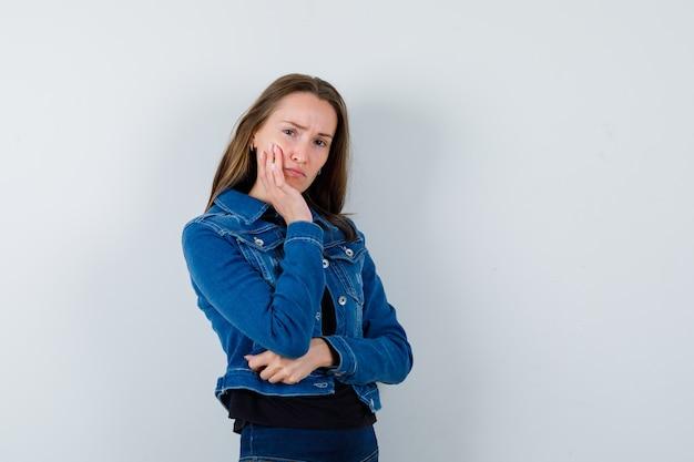 Jovem, apoiando o queixo na palma da mão na blusa, jaqueta e olhando pensativa.