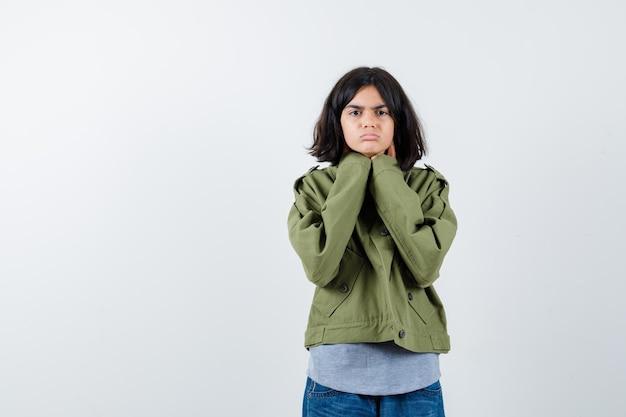 Jovem, apoiando o queixo nas mãos, em suéter cinza, jaqueta cáqui, calça jeans e olhando séria. vista frontal.